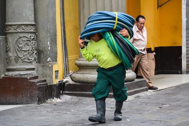 Homem de manutenção carrega mangueiras para regar jardins