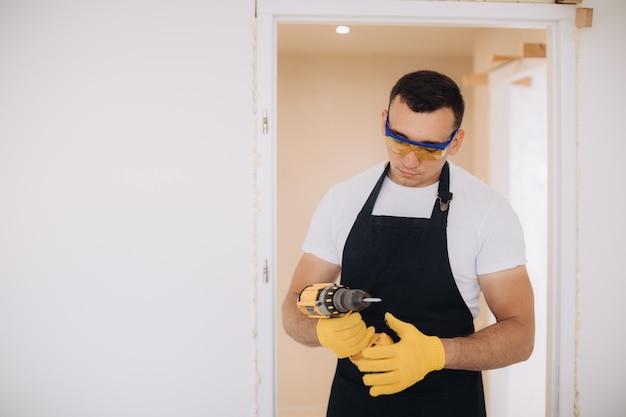 Homem de manutenção que fixa portas com instrumentos
