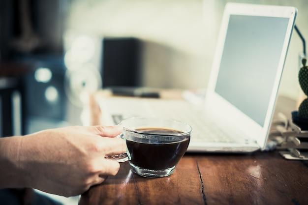 Homem de mão com computador portátil ler notícias de manhã na loja de café