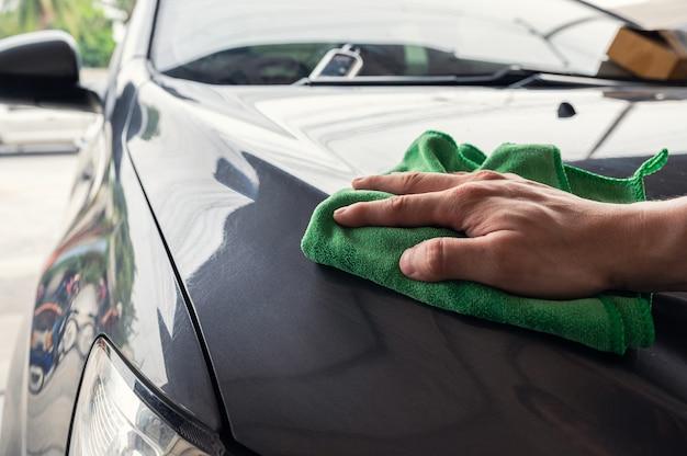 Homem de mão com pano de microfibra verde limpando o capô cinza do carro