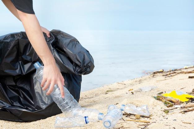 Homem de mão com saco de lixo, pegando a garrafa de plástico na praia