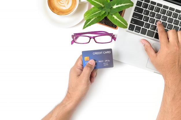 Homem de mão digitando no laptop e usando cartão de crédito para compras on-line na mesa branca