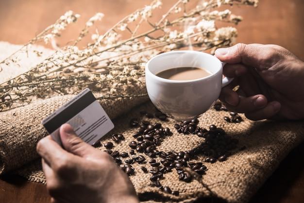 Homem de mão segurando a xícara de café e cartão de crédito