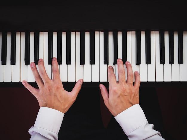 Homem de mão tocando piano. instrumento de música clássica. vista do topo.