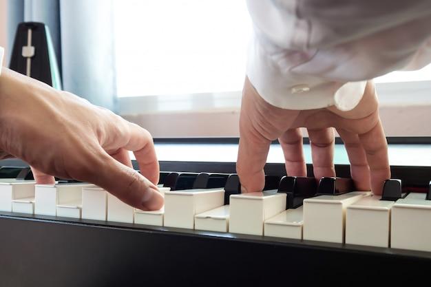Homem de mão tocando piano