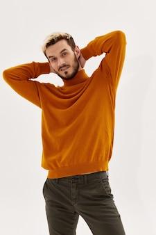 Homem de mãos dadas atrás da cabeça, posando de moda outono estilo estúdio de roupas masculinas