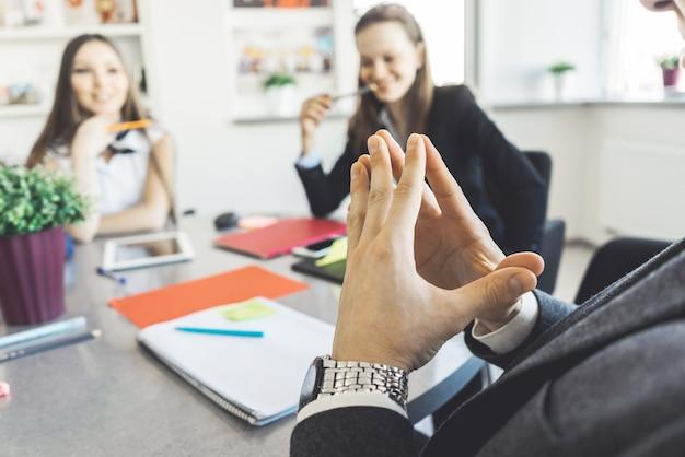 Homem de mãos dadas, usar terno, sentado na reunião de negócios
