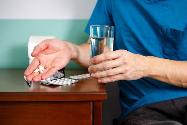 Homem de mãos segurando um comprimido e um copo de água sobre a mesa enquanto está sentado no sofá e vai tomar o remédio