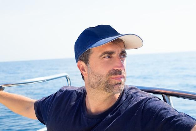 Homem de marinheiro na proa do barco com boné a desviar o olhar do mar