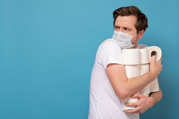Homem de máscara médica segurando um monte de rolos de papel higiênico, escondendo-os de todos