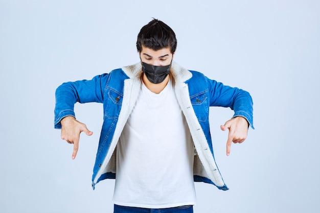 Homem de máscara preta apontando para baixo.