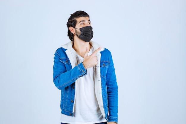Homem de máscara preta apontando para o lado direito.