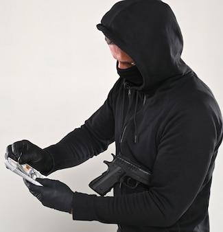 Homem de máscara preta e casaco com capuz com uma arma e um maço de dólares sobre um fundo cinza