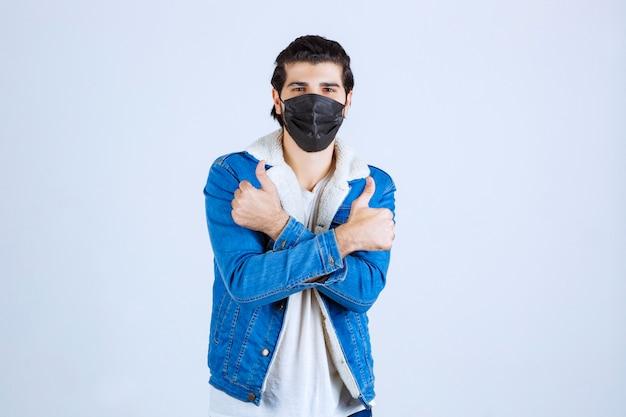 Homem de máscara preta, mostrando sinal de prazer e se sentindo bem.