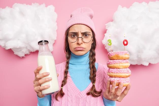 Homem de mau humor celebra seu 30º aniversário sozinho segura rosquinhas com número de velas de aniversário garrafa de leite usa chapéu óculos redondos poses indoor em rosy