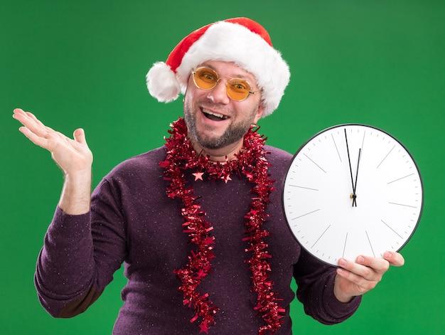 Homem de meia-idade alegre com chapéu de papai noel e guirlanda de ouropel no pescoço, óculos segurando um relógio e mostrando a mão vazia isolada na parede verde