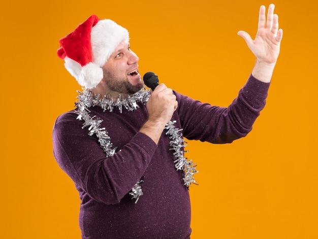 Homem de meia-idade alegre com chapéu de papai noel e guirlanda de ouropel no pescoço segurando o microfone, levantando a mão e cantando isolado em um fundo laranja