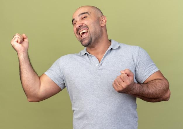 Homem de meia-idade alegre e casual fazendo gesto de sim com os olhos fechados, isolado na parede verde oliva