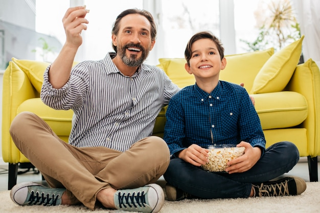 Homem de meia idade alegre passando um tempo com seu filho positivo e sorrindo enquanto assiste tv no chão em casa com pipoca