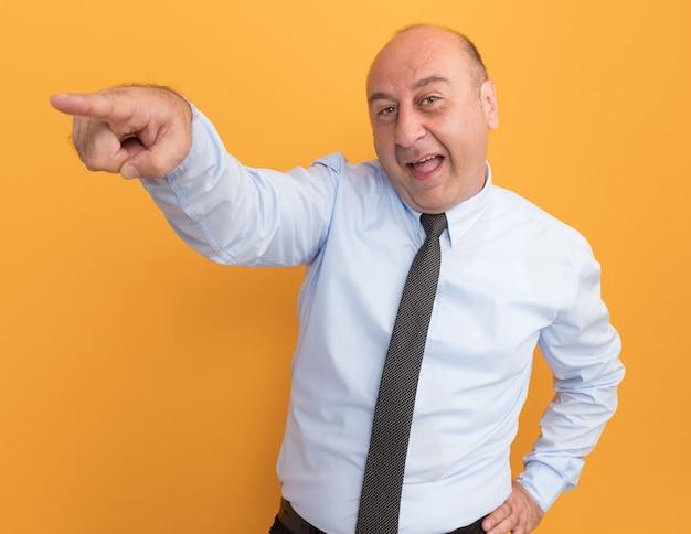 Homem de meia-idade alegre vestindo uma camiseta branca com pontas de gravata na lateral, colocando a mão na cintura isolada em uma parede laranja