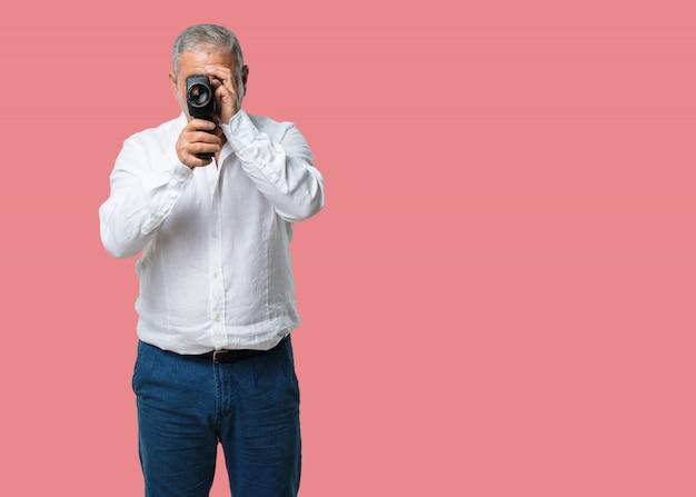 Homem de meia idade animado e entretido, olhando através de uma câmera de filme