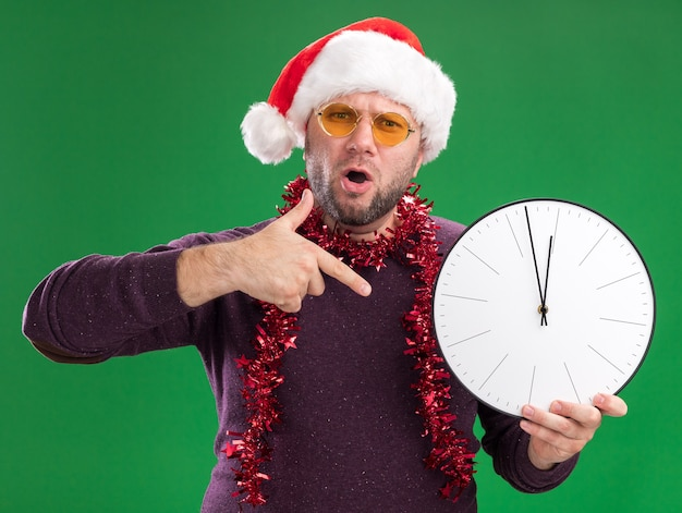 Homem de meia-idade ansioso com chapéu de papai noel e guirlanda de ouropel no pescoço, óculos segurando e apontando para o relógio isolado na parede verde