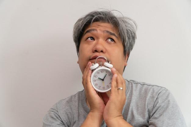 Homem de meia idade asiático está segurando um despertador branco e seu rosto mostrou tédio e se sentindo mal, seu problema é um distúrbio do sono.