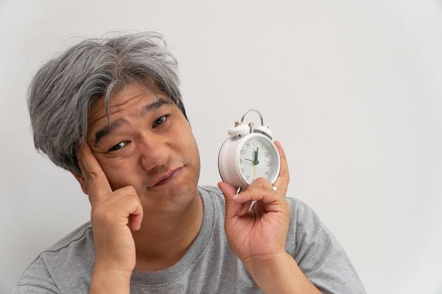 Homem de meia idade asiático está segurando um despertador branco e seu rosto mostrou tédio e se sentindo mal