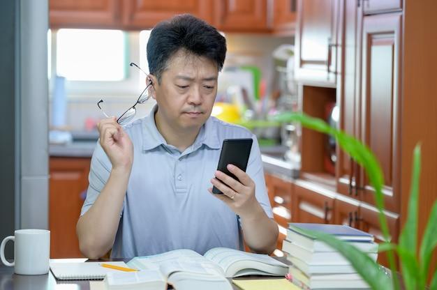 Homem de meia idade asiático sentado na mesa em casa, lendo um livro e estudando.