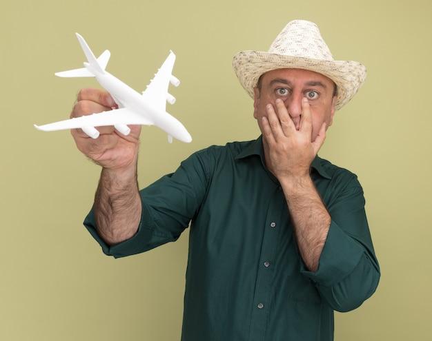 Homem de meia-idade assustado vestindo camiseta e chapéu verdes segurando um avião de brinquedo e colocando a mão na boca isolada na parede verde oliva
