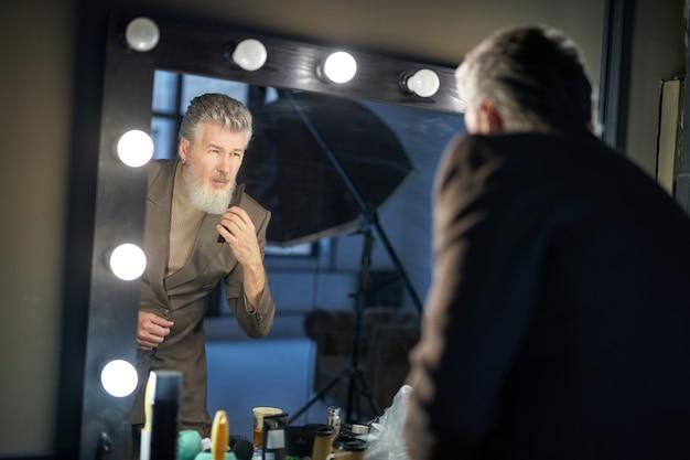 Homem de meia-idade bonito, de cabelos grisalhos, vestindo um terno elegante, olhando-se no espelho