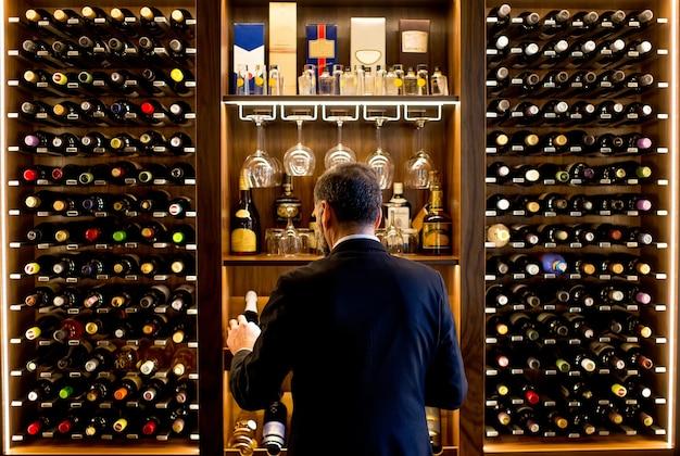Homem de meia idade bonito escolhe uma garrafa de vinho