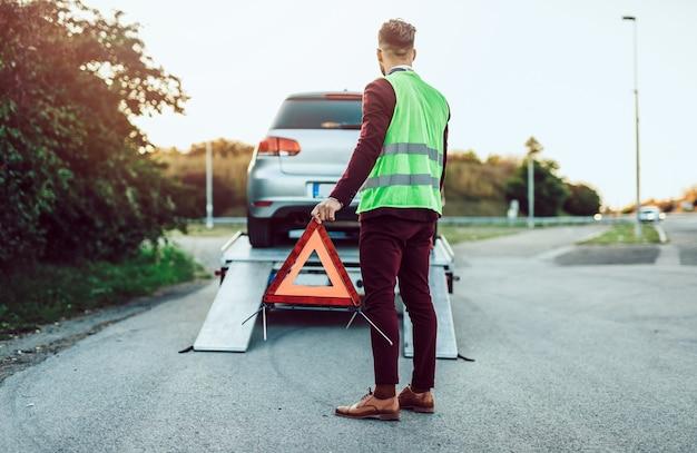 Homem de meia-idade bonito que trabalha no serviço de reboque na estrada. conceito de assistência na estrada.