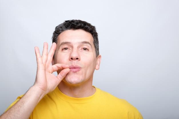 Homem de meia idade branco beija os dedos como um sinal de gostoso