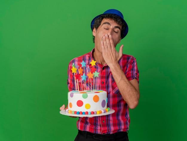 Homem de meia-idade, caucasiano, cansado de festa, usando um chapéu de festa segurando um bolo de aniversário, bocejando, mantendo as mãos na boca com os olhos fechados