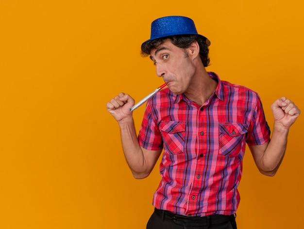 Homem de meia-idade, caucasiano, festeiro, impressionado, olhando para a câmera, mantendo os punhos no ar soprando soprador de festa isolado em um fundo laranja com espaço de cópia