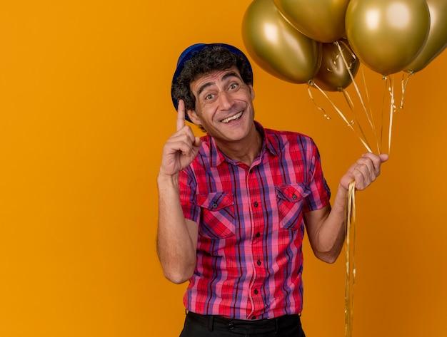 Homem de meia idade, caucasiano, festeiro, impressionado, usando um chapéu de festa e segurando balões, levantando o dedo isolado em um fundo laranja com espaço de cópia