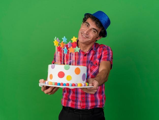 Homem de meia-idade, caucasiano, festeiro sorridente, com chapéu de festa, olhando para a câmera, estendendo o bolo de aniversário em direção à câmera, isolado em um fundo verde com espaço de cópia