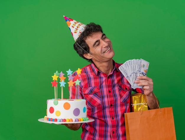Homem de meia-idade, caucasiano, festeiro sorridente, usando um boné de aniversário, segurando um pacote de presente de saco de papel de bolo de aniversário e dinheiro com os olhos fechados