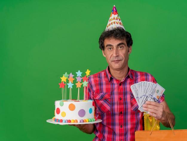 Homem de meia idade, caucasiano, festeiro, usando um boné de aniversário, segurando um bolo de aniversário, um pacote de papel e dinheiro, olhando para a câmera, isolado no fundo verde com espaço de cópia