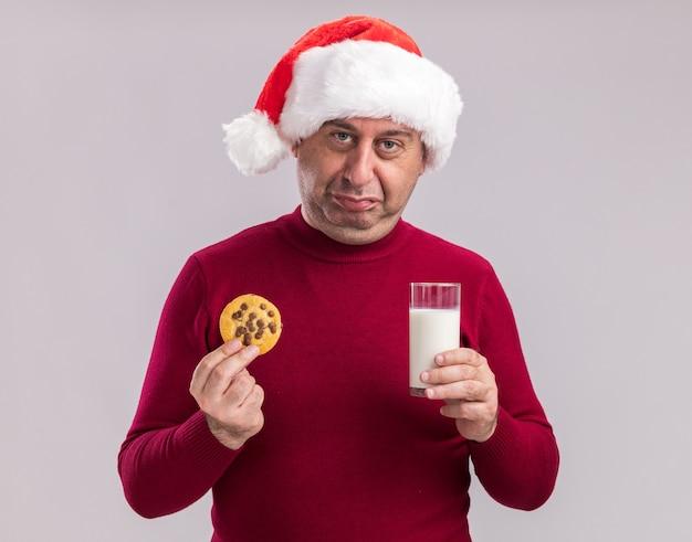 Homem de meia-idade chateado com chapéu de papai noel de natal segurando um copo de leite e biscoito com uma expressão triste em pé sobre uma parede branca
