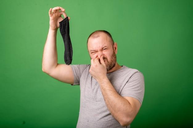 Homem de meia idade cheirando uma meia fedorenta sobre fundo verde. lavanderia, higiene, conceito de pés fedorentos.