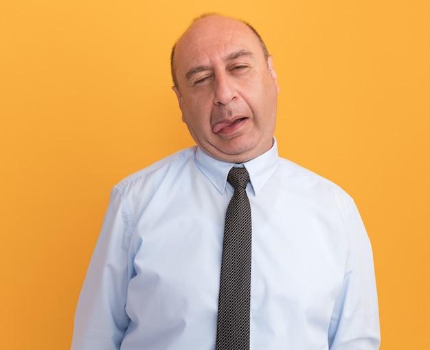 Homem de meia-idade, com a cabeça inclinada e alegre, vestindo camiseta branca com gravata, mostrando a língua isolada na parede laranja