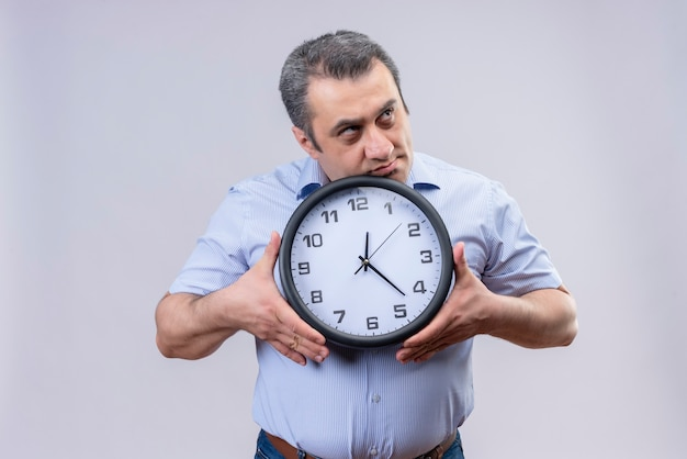 Homem de meia idade com camisa listrada vertical azul, segurando um relógio de parede nas mãos, pensando sobre uma ideia confusa sobre um fundo branco