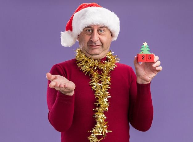 Homem de meia-idade com chapéu de papai noel de natal com enfeites em volta do pescoço segurando cubos de brinquedo com data 25, sorrindo confuso com o braço estendido sobre a parede roxa