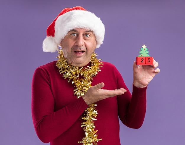 Homem de meia-idade com chapéu de papai noel de natal com enfeites em volta do pescoço segurando cubos de brinquedo com data de 25 anos, apresentando com o braço da mão sorrindo em pé sobre um fundo roxo