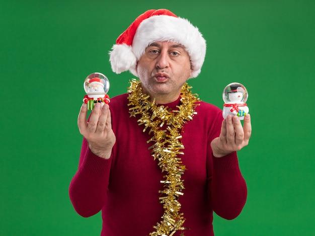 Homem de meia-idade com chapéu de papai noel de natal com enfeites em volta do pescoço segurando globos de neve de natal olhando para a câmera com expressão confiante em pé sobre um fundo verde