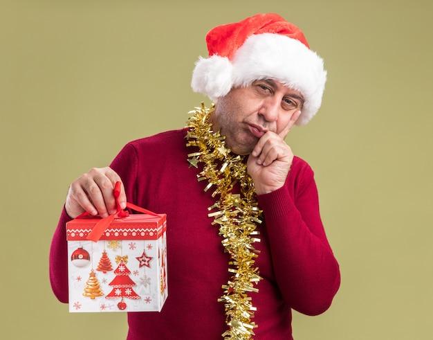 Homem de meia-idade com chapéu de papai noel de natal com enfeites em volta do pescoço segurando um presente de natal olhando para a câmera com a mão no queixo pensando em pé sobre fundo verde