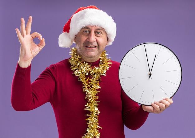 Homem de meia-idade com chapéu de papai noel de natal com enfeites em volta do pescoço segurando um relógio de parede, olhando para a câmera, sorrindo mostrando uma placa de ok em pé sobre um fundo roxo