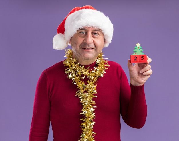 Homem de meia-idade com chapéu de papai noel de natal com enfeites no pescoço segurando cubos de brinquedo com data de 25 anos olhando para a câmera sorrindo em pé sobre fundo roxo